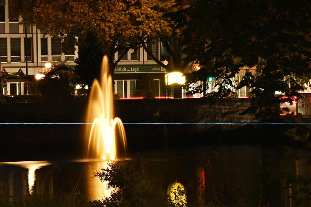 Leuchtender, hellblauer Draht schwebt vor dem gelb beleuchteten Springbrunnen an der Alten Post