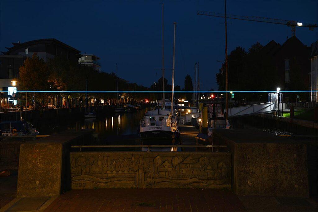 Hellblau leuchtender Draht über dem Gelände am Oldenburger Hafen