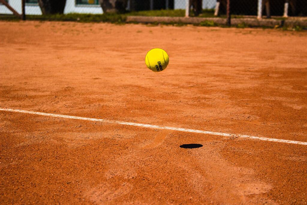 Der Tennisball fliegt nah an der Linie auf dem Außenplatz