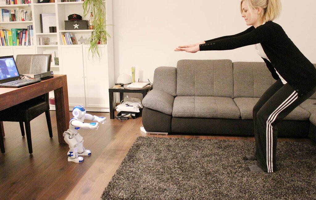 Roboter NAO zeigt und analysiert eine Kniebeuge zuhause, Einfaches aber richtiges Training neben der Couch durch NAO