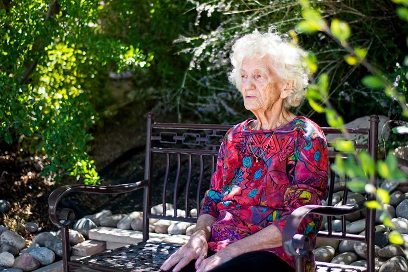 Ältere Dame auf einer Bank sitzend